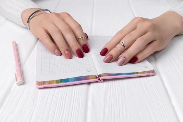 Mãos de mulher com design minimalista de primavera rosa verão manicure na mesa do escritório