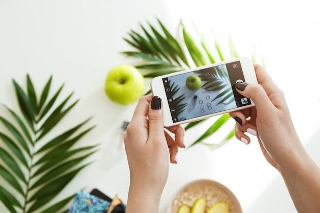 Mãos de mulher com elegante esmalte segurando o telefone tirando fotos.