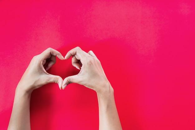 Mãos de mulher com forma de coração em fundo vermelho com espaço para cópia