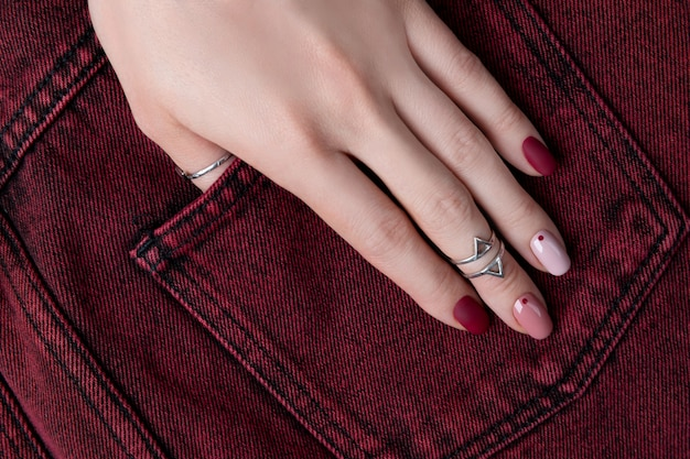 Mãos de mulher com jóias de prata e acessórios. mulher com design minimalista primavera rosa verão manicure.