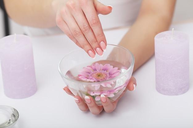 Mãos de mulher com lindas unhas de manicure francesa