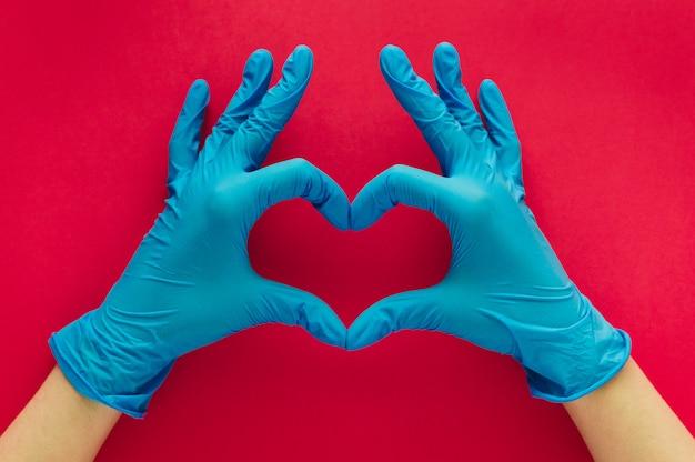 Mãos de mulher com luvas azuis formando um coração com os dedos em um fundo vermelho