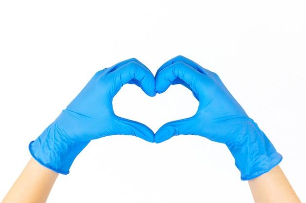 Mãos de mulher com luvas azuis formando um coração com os dedos isolados no branco