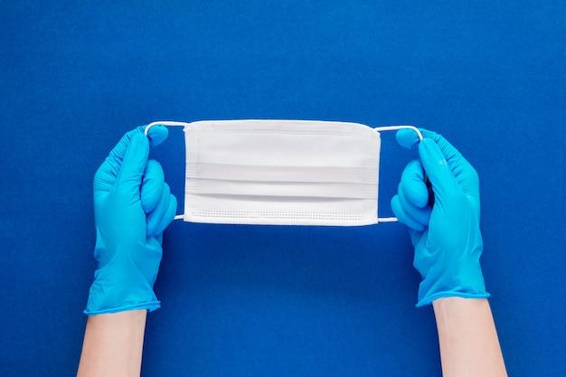 Mãos de mulher com luvas azuis segurando uma máscara facial em um plano de fundo texturizado azul