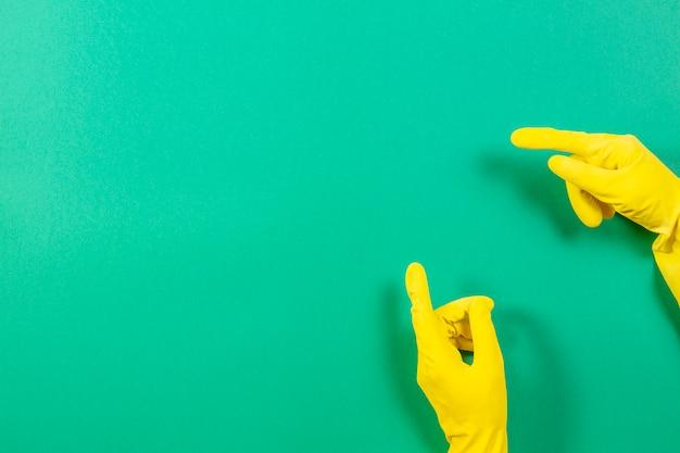 Mãos de mulher com luvas de borracha amarela aponta para cima com o dedo, sobre fundo verde