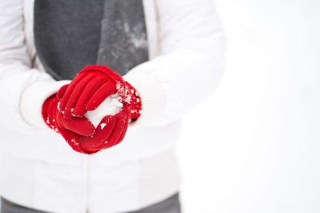 Mãos de mulher com luvas vermelhas fazendo uma bola de neve
