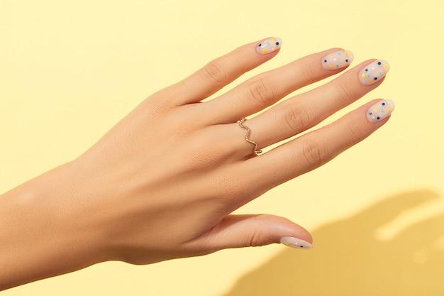 Mãos de mulher com manicure de bolinhas da moda sobre fundo amarelo