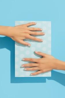 Mãos de mulher com manicure de bolinhas na moda no fundo azul
