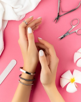 Mãos de mulher com manicure francesa branca na moda