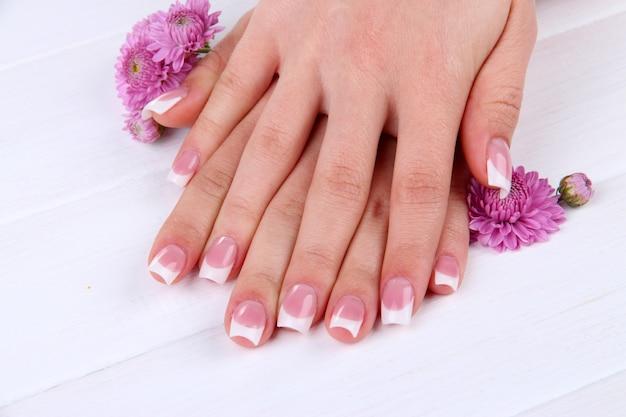 Mãos de mulher com manicure francesa e flores sobre fundo branco de madeira