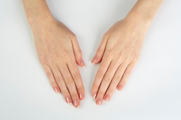 Mãos de mulher com manicure francesa