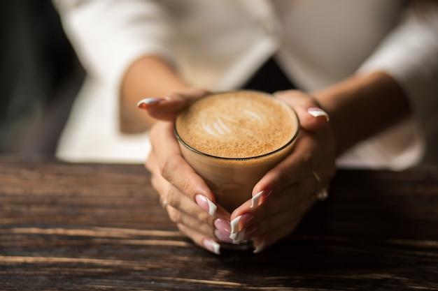 Mãos de mulher com manicure linda close-up segurar um copo com café quente em uma mesa de madeira