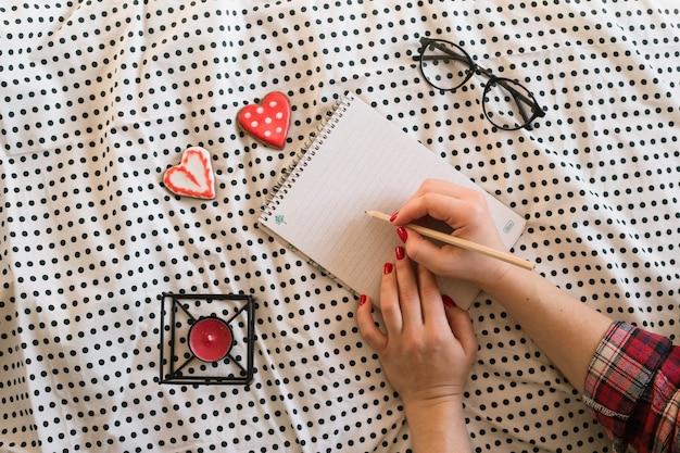 Mãos de mulher com manicure perfeita segurando um lápis e um bloco de notas em espiral
