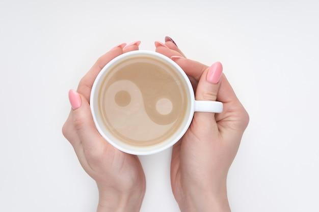 Mãos de mulher com manicure rosa, segurando a xícara de café com leite com a imagem de yin e yang,