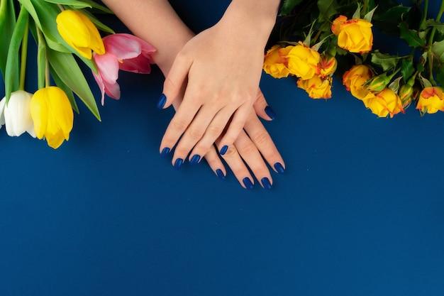 Mãos de mulher com manicure segurando tulipas coloridas