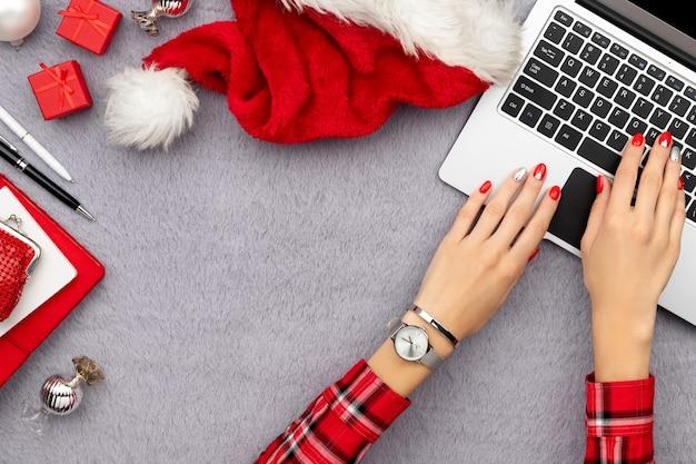 Mãos de mulher com manicure vermelha moderna digitando no teclado