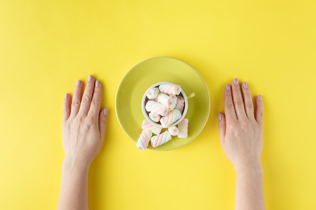 Mãos de mulher com marshmallow torcido no fundo vibrante