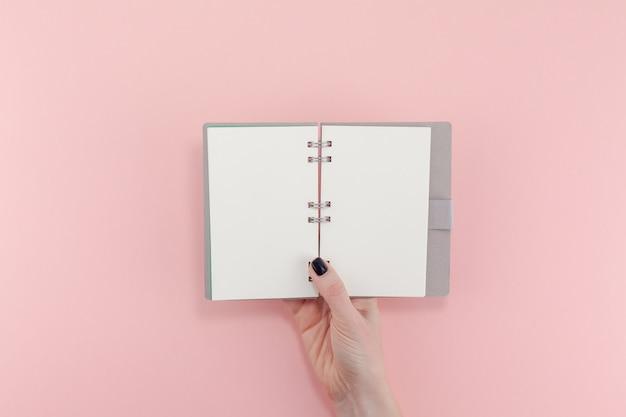 Mãos de mulher com o bloco de notas em branco