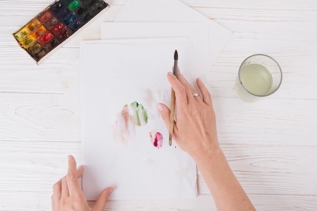 Mãos de mulher com pincel perto de papel com borrões, vidro e conjunto de cores de água