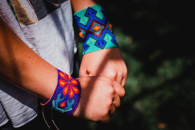 Mãos de mulher com pulseira colorida feita à mão