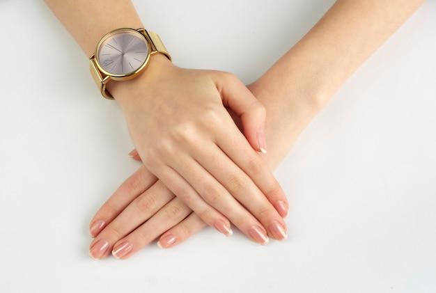 Mãos de mulher com relógio de ouro