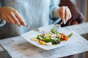 Mãos de mulher com salada Caesar na mesa no restaurante