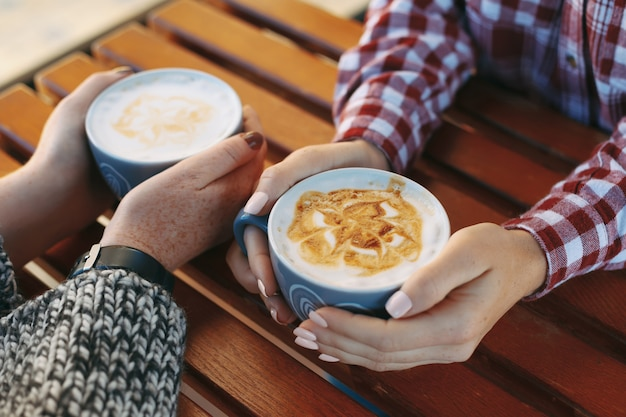 Mãos de mulher com sardas segurando xícaras de café