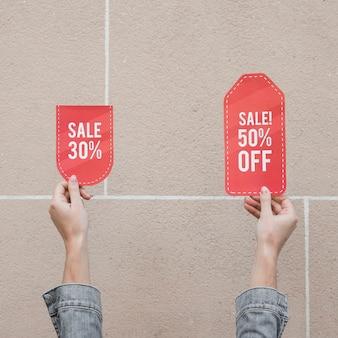 Mãos de mulher com sinais de venda