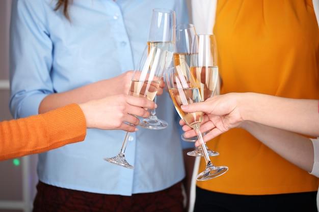 Mãos de mulher com taças de champanhe
