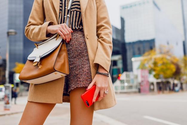 Mãos de mulher com telefone celular. menina elegante com casaco bege conversando. cidade moderna.