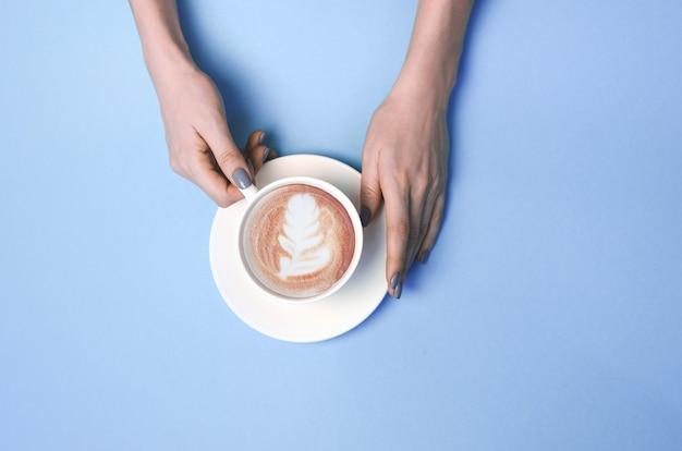 Mãos de mulher com uma xícara de café com latte art