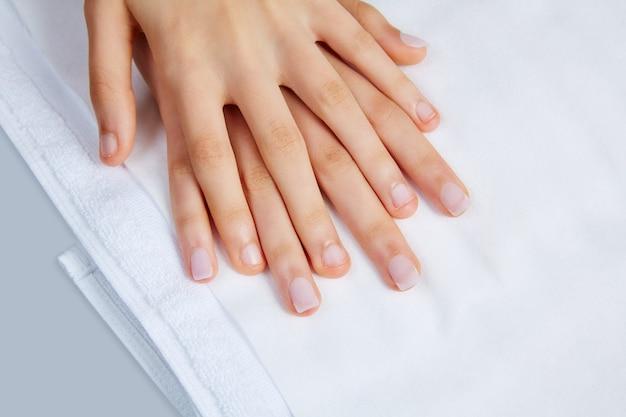 Mãos de mulher com unhas antes do tratamento