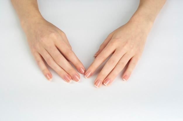 Mãos de mulher com unhas polidas