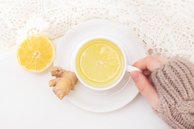 Mãos de mulher com vista de cima de chá de limão