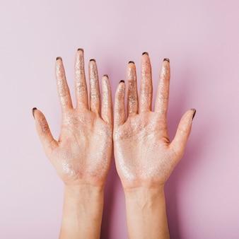 Mãos de mulher com vista superior de glitter prata