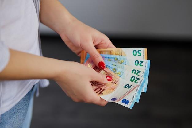 Mãos de mulher contando dinheiro euro, segurando nas mãos dela.