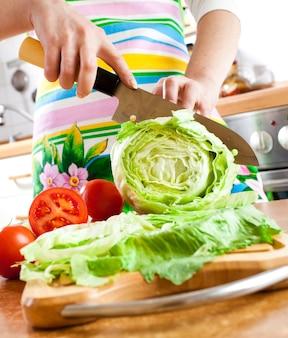 Mãos de mulher cortando alface, atrás de legumes frescos.