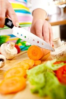 Mãos de mulher cortando cenoura, por trás de legumes frescos.