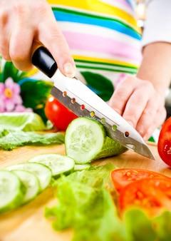 Mãos de mulher cortando pepino, atrás de legumes frescos.