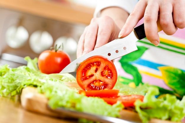 Mãos de mulher cortando tomate, por trás de legumes frescos.
