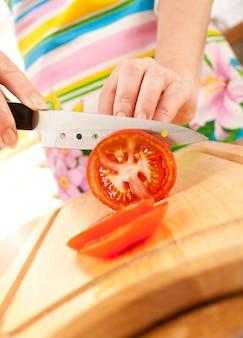 Mãos de mulher cortando tomate, uma faca afiada.