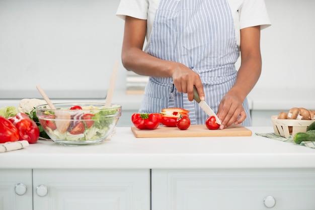 Mãos de mulher cortando tomates frescos para salada