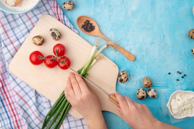 Mãos de mulher, corte a cebolinha e outros alimentos e legumes na mesa azul