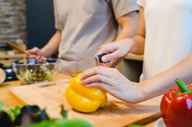 Mãos de mulher, corte o pimentão na cozinha