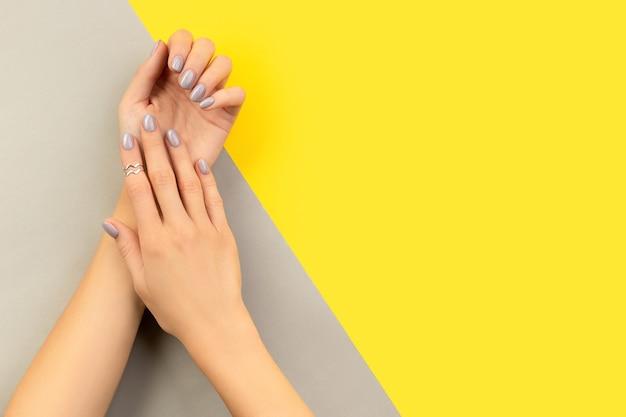 Mãos de mulher cuidadas com unhas brilhantes em cinza e amarelo