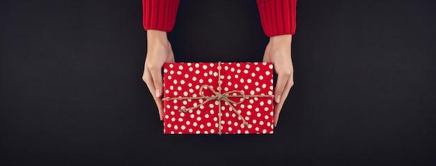 Mãos de mulher dando caixa de presente de natal em fundo preto