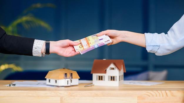 Mãos de mulher dando dinheiro para casa nova, plana para o corretor de imóveis.
