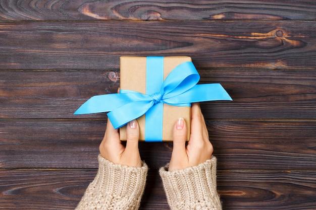 Mãos de mulher dão caixa de presente