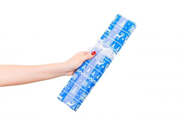 Mãos de mulher dão embrulhado natal ou outro feriado artesanal presente em papel azul com fita branca.