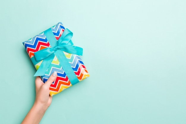 Mãos de mulher dão embrulhado natal ou outro presente artesanal de férias em fundo de papel colorido
